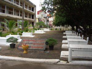 左に見えるのがトゥール・スレンのA棟。手前はクメール・ルージュが逃走した時に残されていた遺体を埋葬した墓