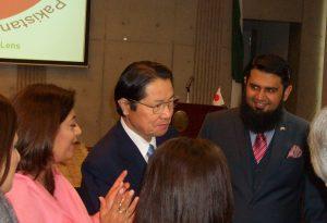 カディール氏(左)が日本・パキスタン友好議員連盟会長の衛藤氏(中央)に写真について説明している。右はサルマン・ババール臨時代理大使。